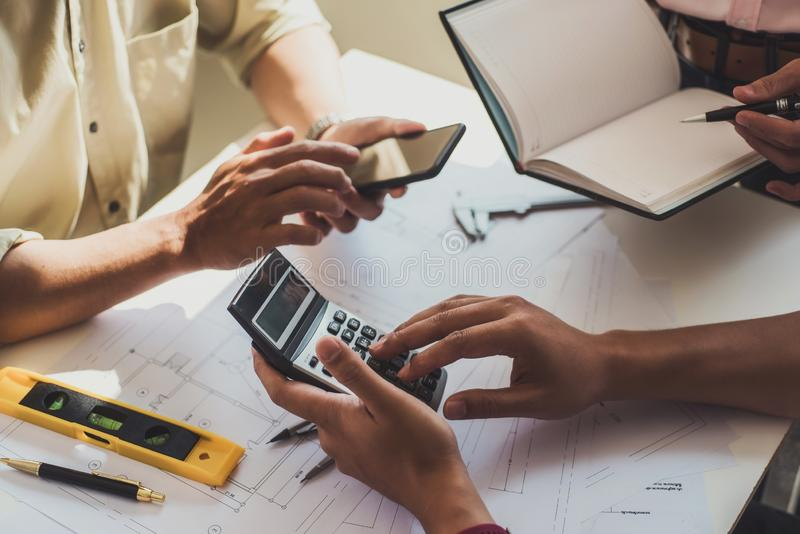 Close up hand of civil engineer or architect business using calculator about calculate the cost with for working building plan royalty free stock photos