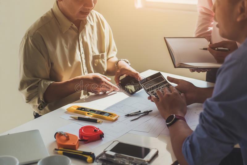 Close up hand of civil engineer or architect business using calculator about calculate the cost with for working building plan stock photo
