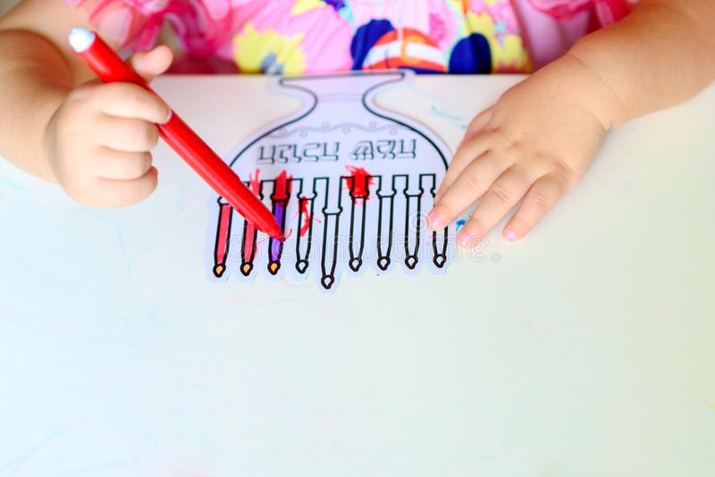 Close up hand cute little toddler kid painting with color pen paper menorah and candle Jewish holiday Chanukah. royalty free stock images