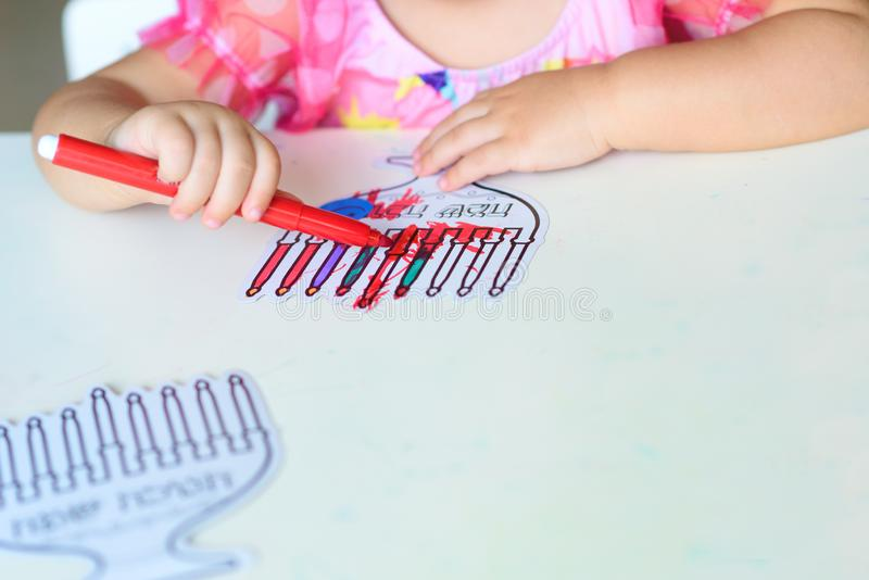 Close up hand cute little toddler kid painting with color pen paper menorah and candle. stock image