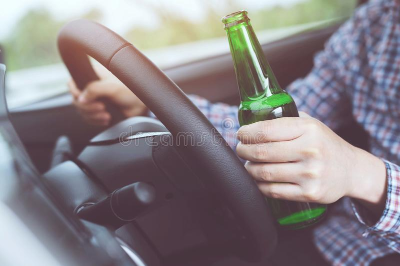 Close up hand Drunk young man while driving a car with a bottle of beer. Don`t drink and drive concept. Driving royalty free stock photography