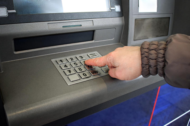 Close up of hand entering pin at an ATM. Female arms, ATM - entering pin.Woman using banking machine. royalty free stock image