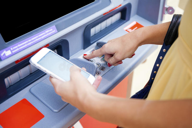 Close up of hand entering pin at an ATM. Finger about to press a. Pin code on a pad. Security code on an Automated Teller Machine. Female arms, ATM - entering stock photo