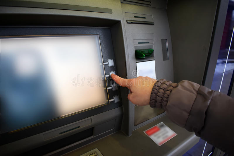 Close up of hand entering pin at an ATM. Woman using banking machine royalty free stock images