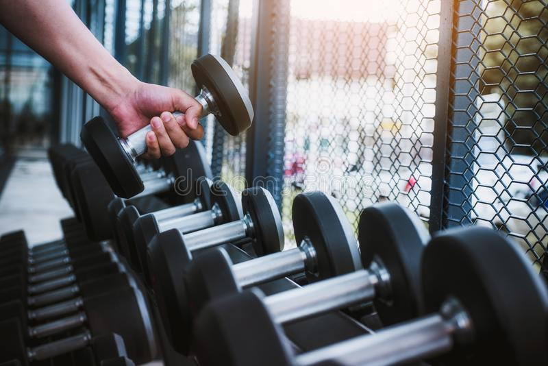 Close up of hand exercise man with dumbbell for flexing muscles in gym. healthy lifestyle Concept royalty free stock photos