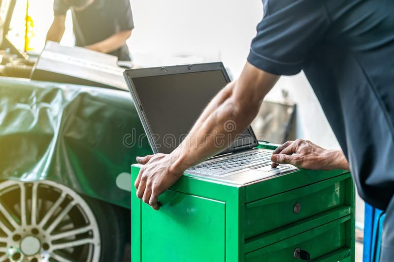 Close up hand finger of repairman touch laptop or computer notebook interfaced with car for repair during work investigate problem stock photography