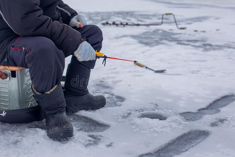Close-up hand of fisherman catches fish on winter fishing rod on frozen river with hole royalty free stock images