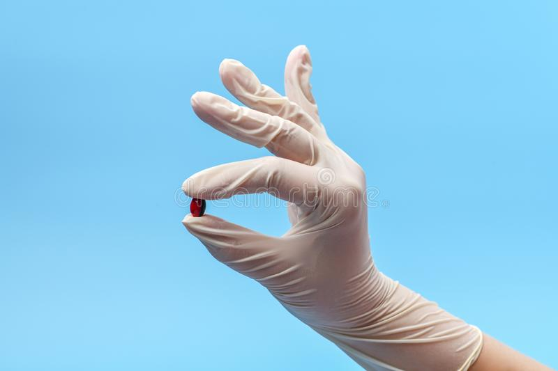 Close-up of a hand fragment in a white medical glove holding one pill, capsule on a blue background. royalty free stock image