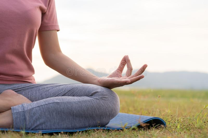 Close up hand and half body of health woman sit in lotus yoga position in the morning at park. Practicing yoga makes meditation. For healthy breathing  and royalty free stock photos