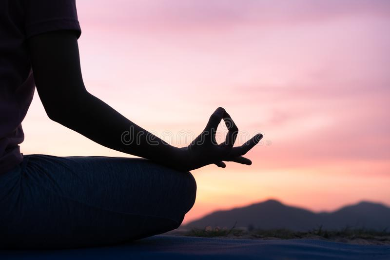 Close up hand and half body of health woman sit in lotus yoga position in the  sunset Practicing yoga makes meditation for healthy. Breathing  and relaxation stock photography