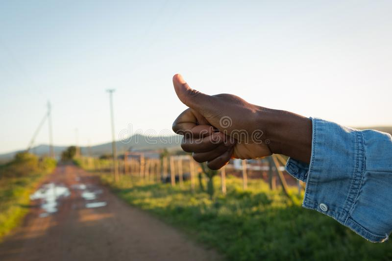 Hand hitchhiking on a sunny day. Close-up of hand hitchhiking on a sunny day royalty free stock photography