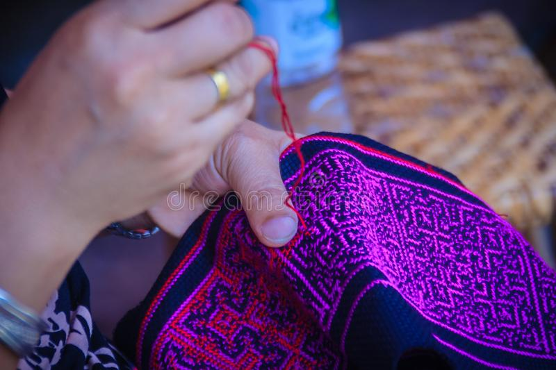 Close up hand of Hmong woman is sewing traditional tribal clothe. S with sewing needle and thread at Doi Pui's Hmong ethnic hill-tribe village, Chiang Mai royalty free stock photo