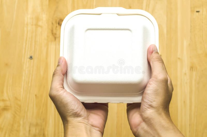 Close up hand  hold cake dessert in unmarked clear empty blank cardboard box, food order .Delivery concept.  Advertising area. Cardboard box stock images