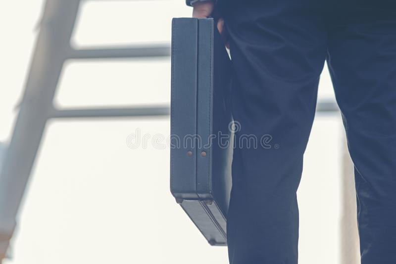 Close up hand holding business bag on the street. Unrecognizable businessman walking with a briefcase in a modern office. stock photos