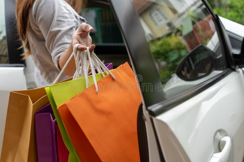 Close up hand holding car remote key open car door. Girl holding colorful shopping bags. Shopping lifestyle concept royalty free stock images