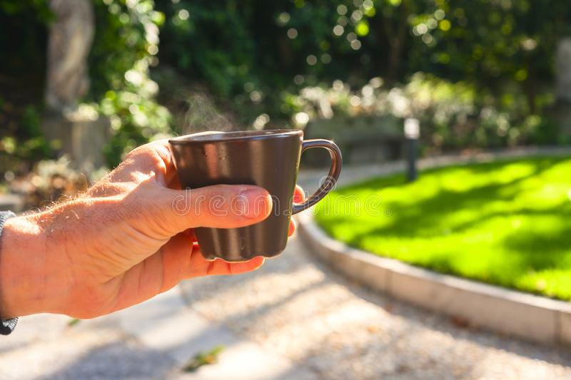 Close up hand holding coffee cup with nature on background. Drinking at outdoor cafe.  royalty free stock image