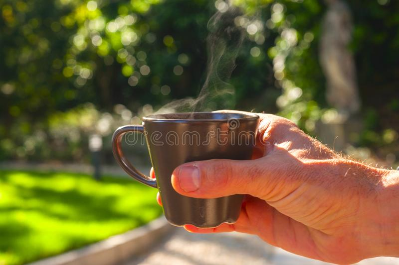 Close up hand holding coffee cup with nature on background. Drinking at outdoor cafe.  stock photo