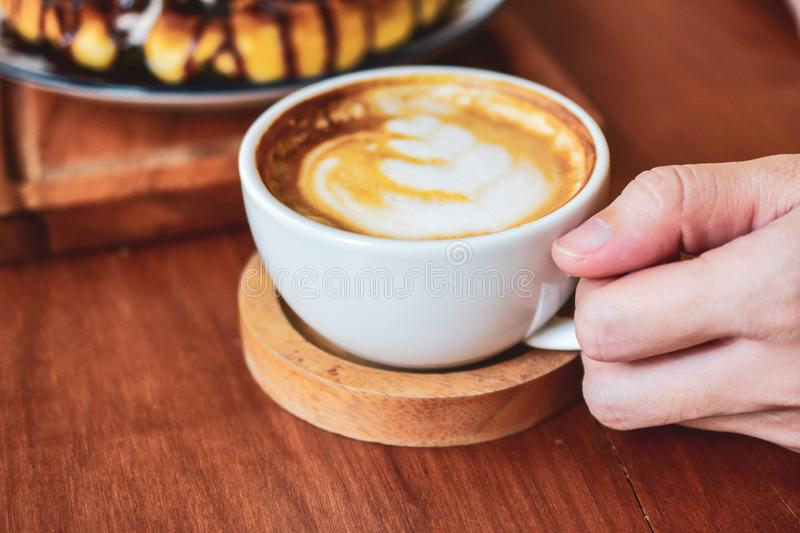 Close up Hand holding coffee cup of  People are in coffee shop. And drink stock images