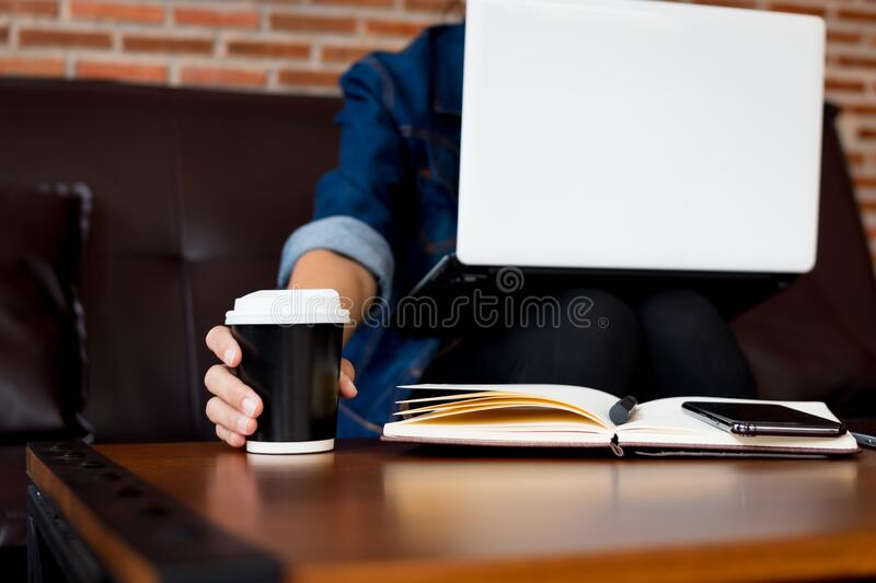 Close up hand holding coffee cup during work at cafe.  royalty free stock photo