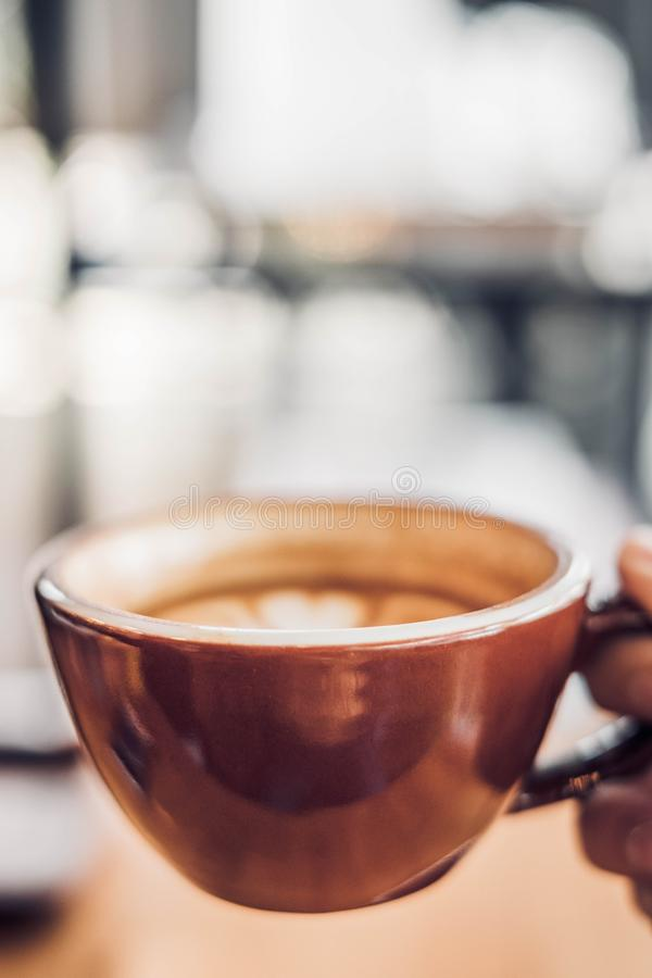 Close up hand holding a cup of hot cappuccino coffee cup with heart shape latte art blur cafe interior.food and drink concept.copy stock image