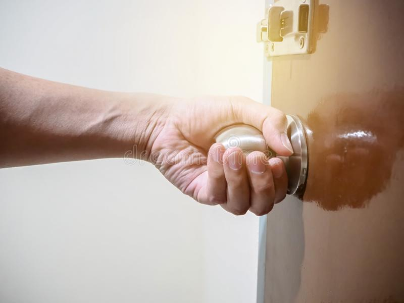 Close up of hand holding a door knob, opening or closing the door. stock photography