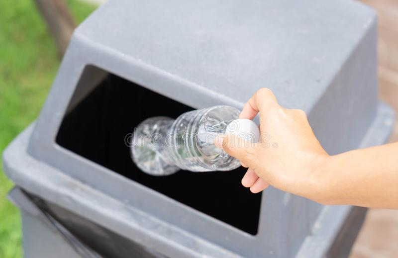 Close up hand holding garbage plastic bottle into recycle trash bin, selective focus royalty free stock image