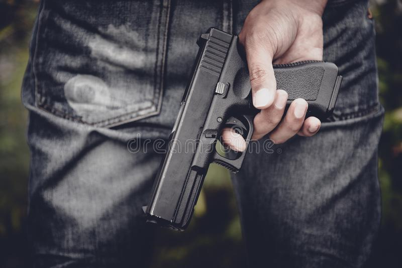 Close up of hand holding handgun in behind. Weapon and dangerous equipment concept. Criminal and Social issues theme stock photography