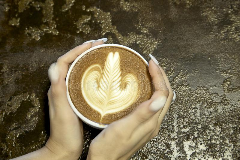 Close-Up Of Woman Holding Coffee. Close up Of Hand Holding Hot Latte Art Coffee Served On Table royalty free stock photo