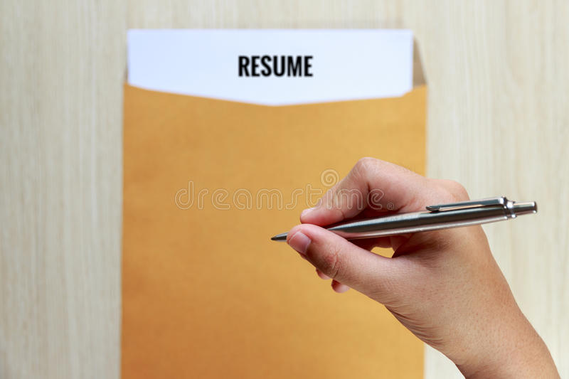 close up hand holding pen over the resume in envelope stock image