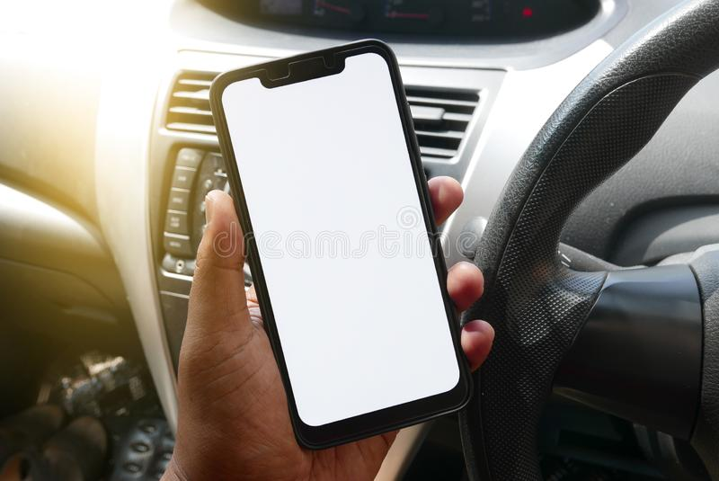 Close up of hand holding phone with white screen inside a car. Smartphone with mockup on background of car dashboard royalty free stock photo