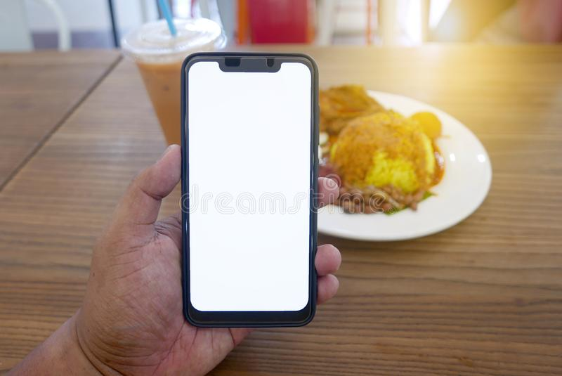 Close up of hand holding phone with white screen. Smartphone with mockup on background of cafeteria or restaurant royalty free stock image