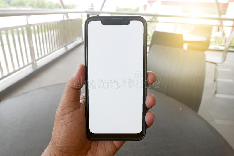 Close up of hand holding phone with white screen. Smartphone with mockup on background of cafeteria or restaurant stock photo