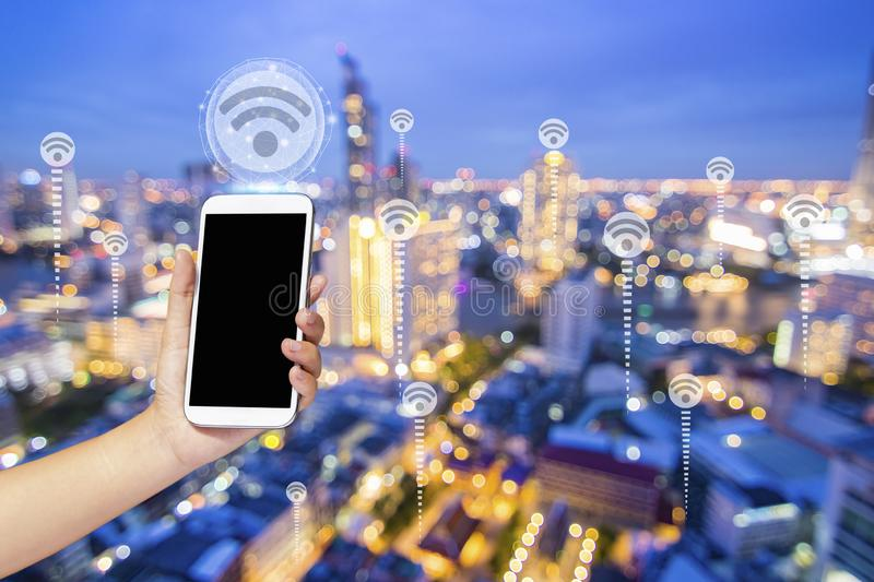Close up hand holding phone with WiFi icon over night city, internet and connection concept royalty free stock photography