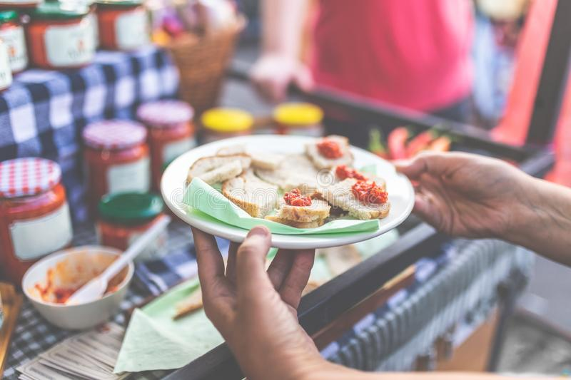 Hands offering small bread slices with traditional ajvar at market stall. Close up of hand holding plate with bread slices and ajvar samples at street market stock photo