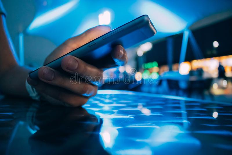 Close-up hand holding smart phone on night bar stock images