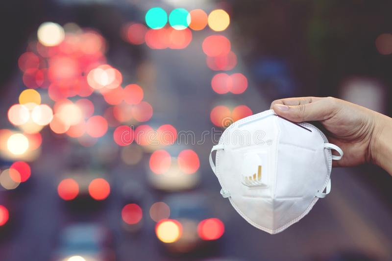 Close up hand holding submit wearing facial hygienic mask nose outdoor. Ecology, air pollution car, Environmental and virus protection concept flu health stock image