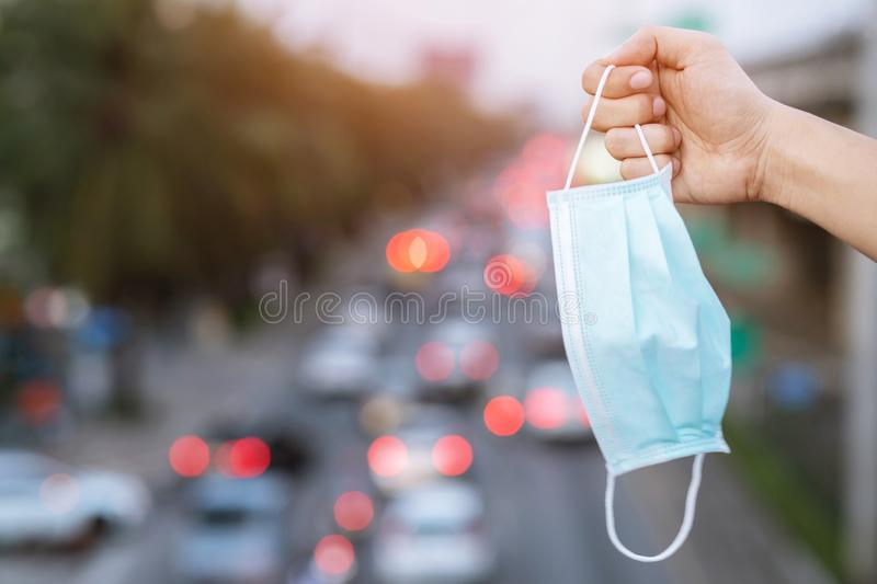 Close up hand holding submit wearing facial hygienic mask nose outdoor. Ecology, air pollution car, Environmental and virus protec royalty free stock images