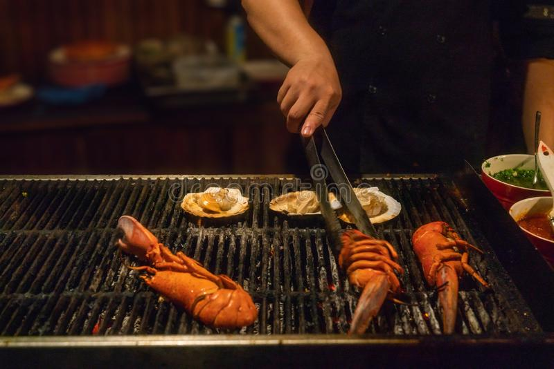 Close up of hand holding tongs and grilling lobster. Human hand holding tongs and grilling lobster on barbecue pan royalty free stock photography
