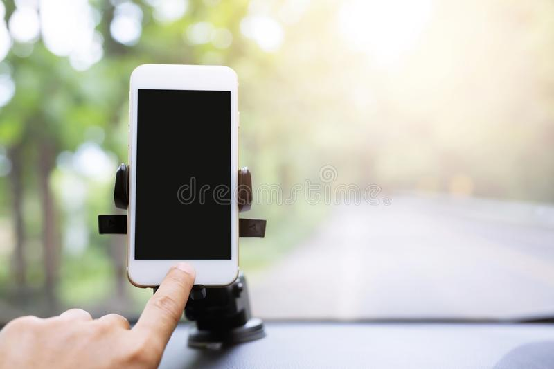 Close up hand holding using mobile smart phone with black screen in car console front windshield holder stick. insert map gps navi stock photos