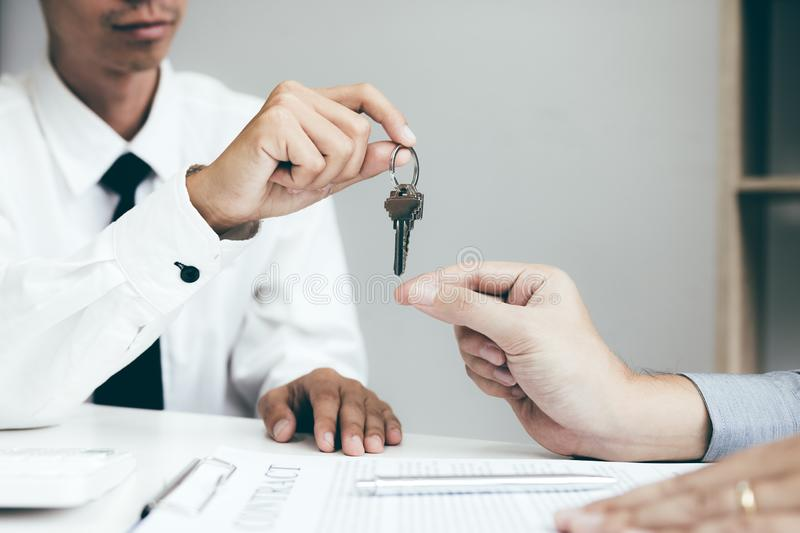 Close up hand of home agents are handing out keys to new home buyers.  royalty free stock images