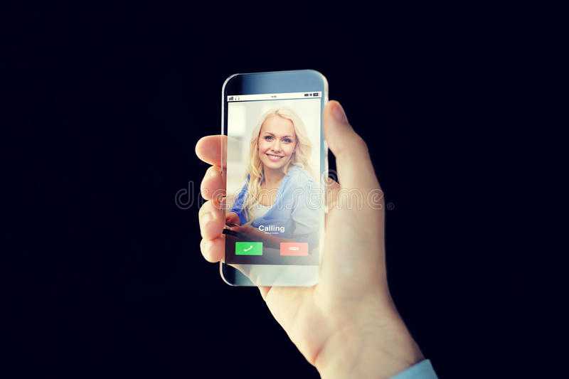 Close up of hand with incoming call on smartphone. Business, future technology and people concept - close up of male hand holding and showing transparent stock photography