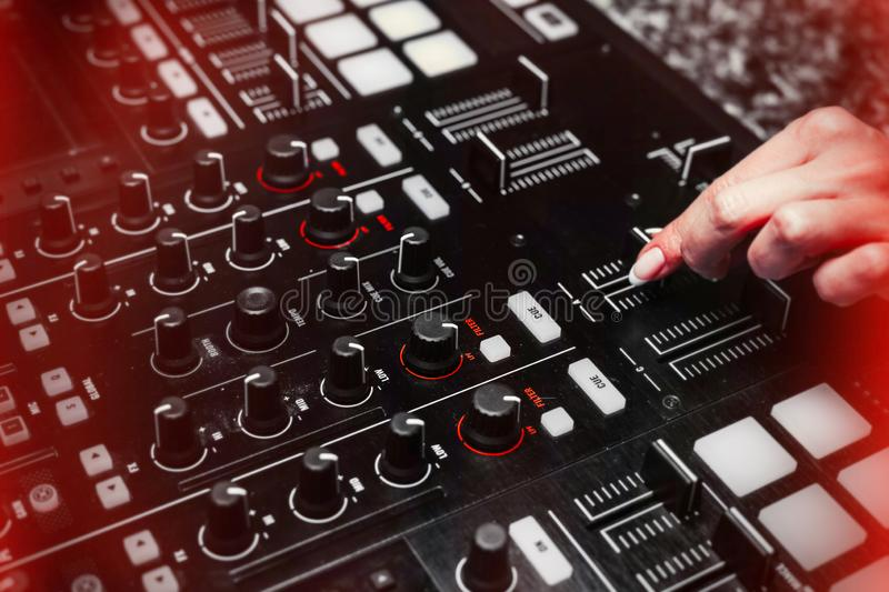 Close up of Hand Increasing Sound of DJ Instrument, Moving Fader. royalty free stock image