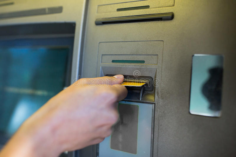 Close up of hand inserting card to atm machine stock image