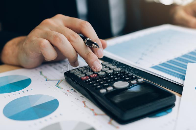 Close up of hand investors are using calculators to calculate the company`s earnings to invest in stocks for future profits.  royalty free stock photos