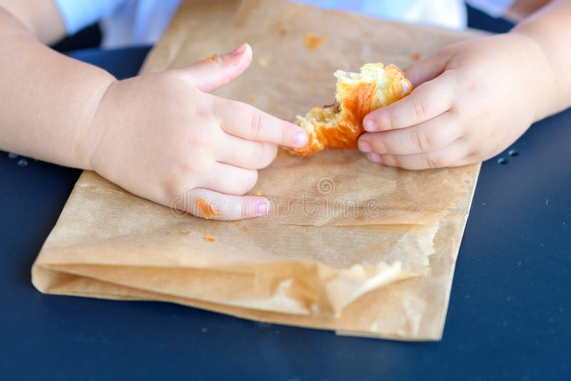 Close up kid hands holding croissant. stock image