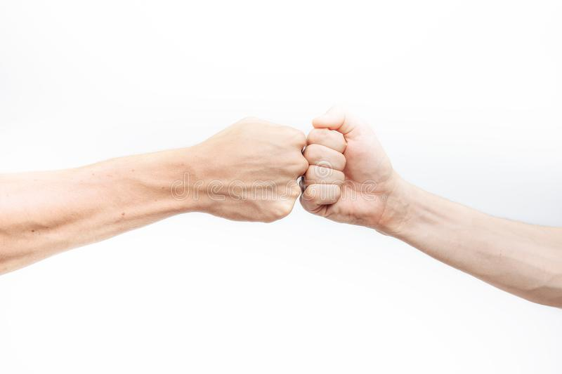 Close-up of the hand, makes a fist kick on a white background. Business people make a Cam pump together after a good deal. The con stock photography
