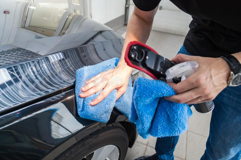 Close-up on the hand of a male cleaner with a blue microfiber cloth that wipes a black car after applying a protective coating stock photo