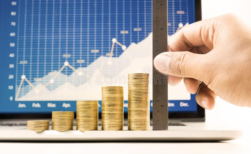 Close up hand male measuring coin stacked stock photo
