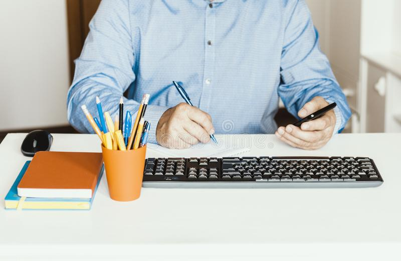 Close-up of hand man using a mouse and typing on keyboard on white table, business concept stock image