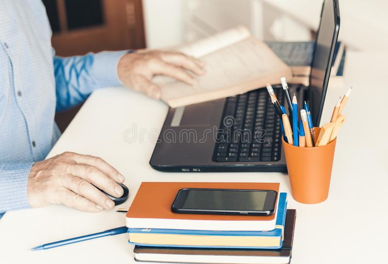 Close-up of hand man using a mouse and typing on laptop on white table, business concept stock image